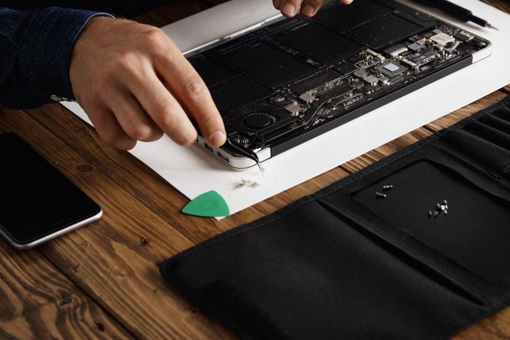 Close-up of technician repairing macbook