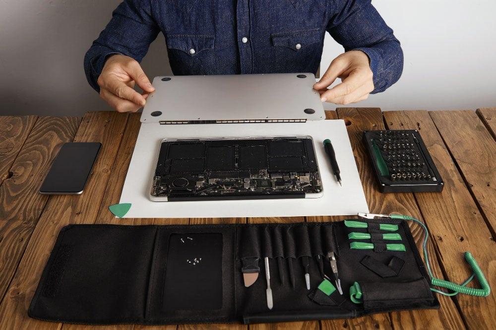 macbook repair technician fixing macbook base plate